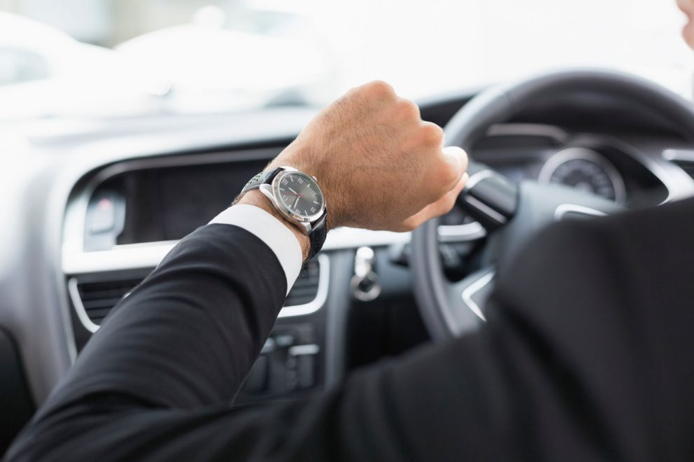 business men in car with watch